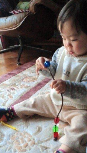 家でならこんな紐通しも(1歳3ヵ月)紐の先をテープでしっかり巻いておくのがコツ