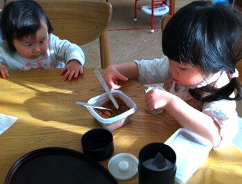 年齢の近い子どもの動きは見やすい <br> お茶をパックに入れる4歳とじっと見る妹<br>