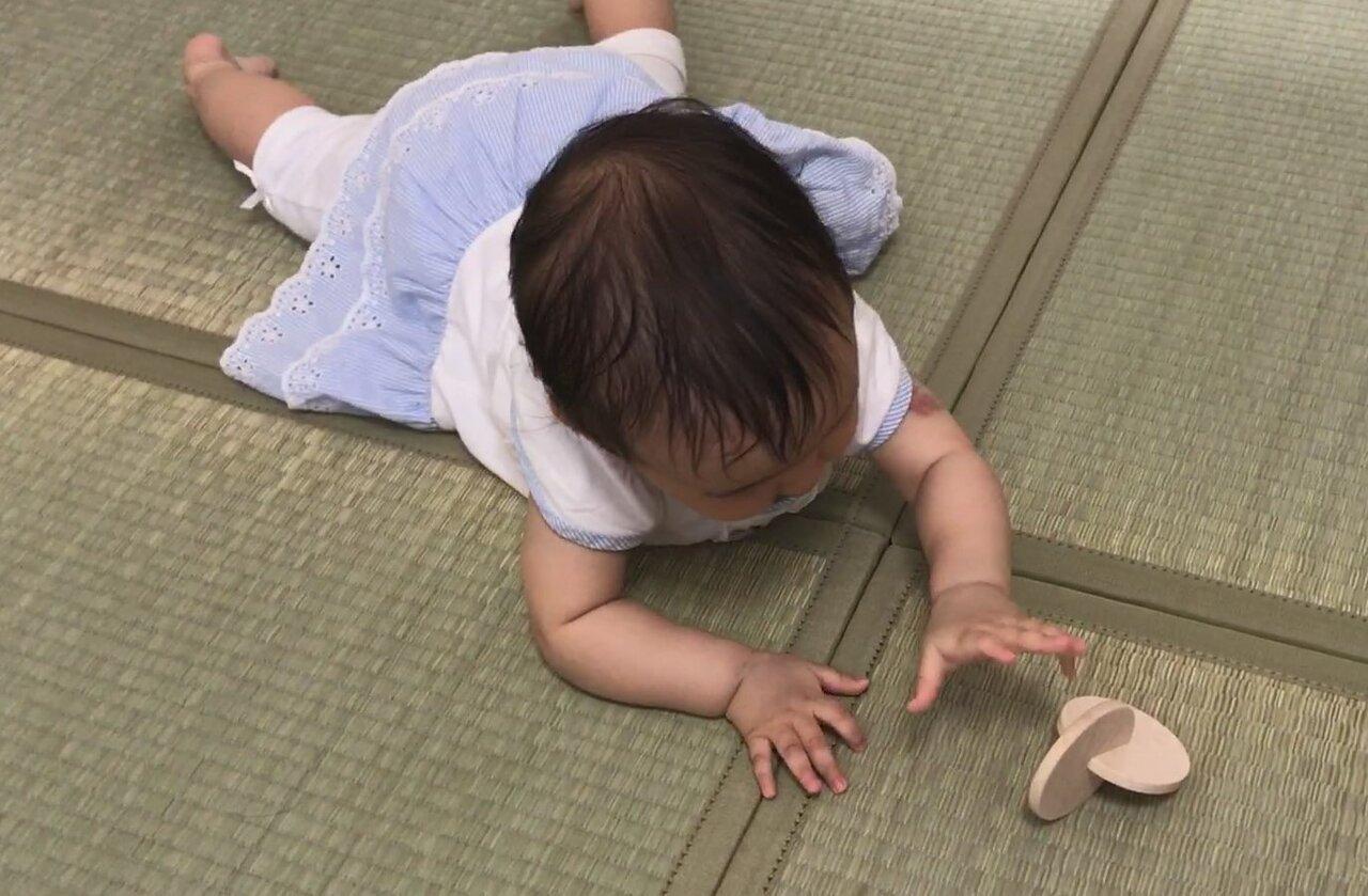 ずりばいで手を伸ばす赤ちゃん