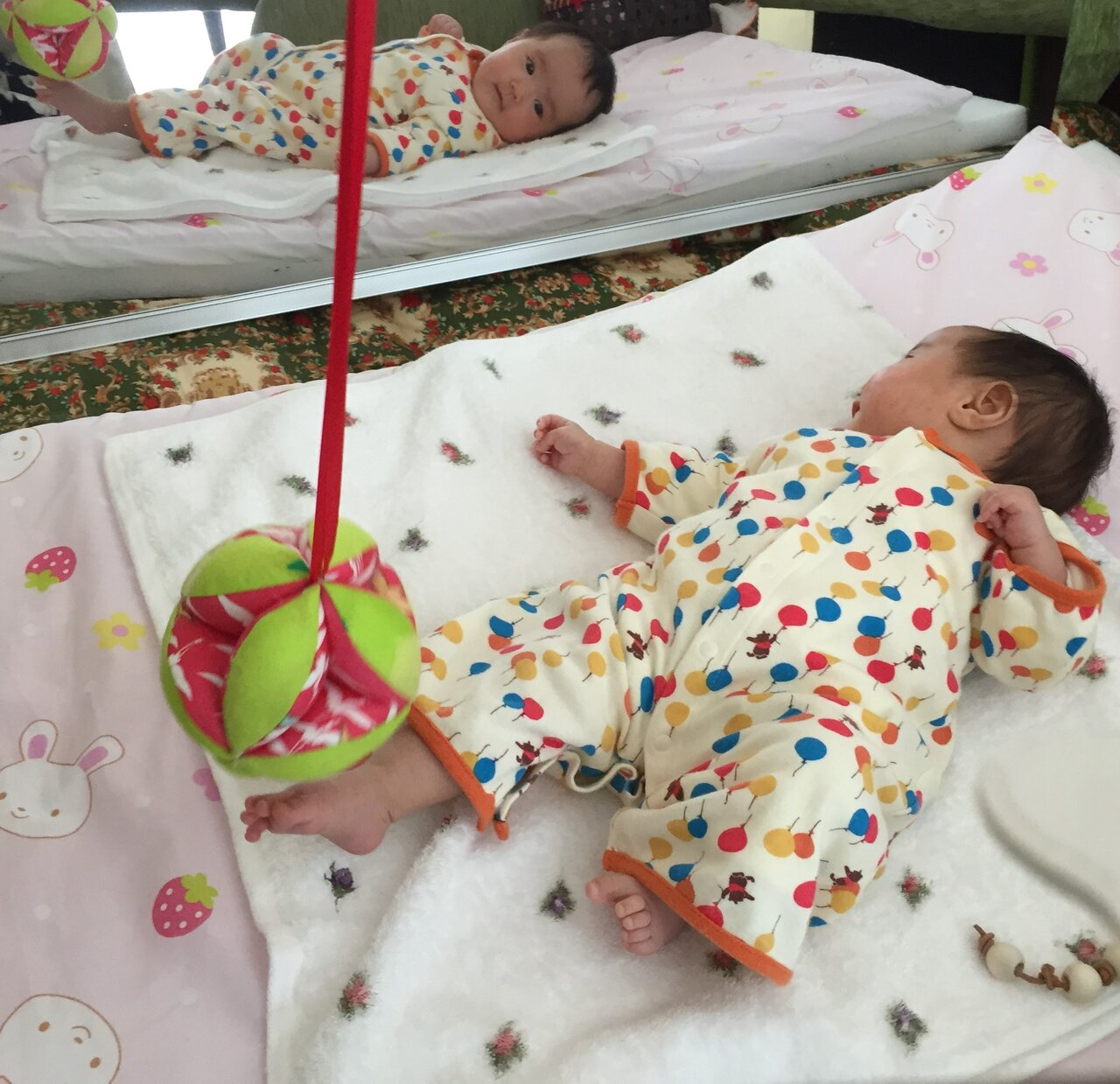 鏡を見てボールを蹴る赤ちゃん