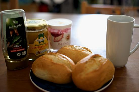 """左からアガベシロップ、蜂蜜、ルビーチョコクリームと""""シュリッペ""""(ドイツの小さなパン)。「これが我が家のシンプルな朝ごはんです」。  写真提供:希代真理子"""