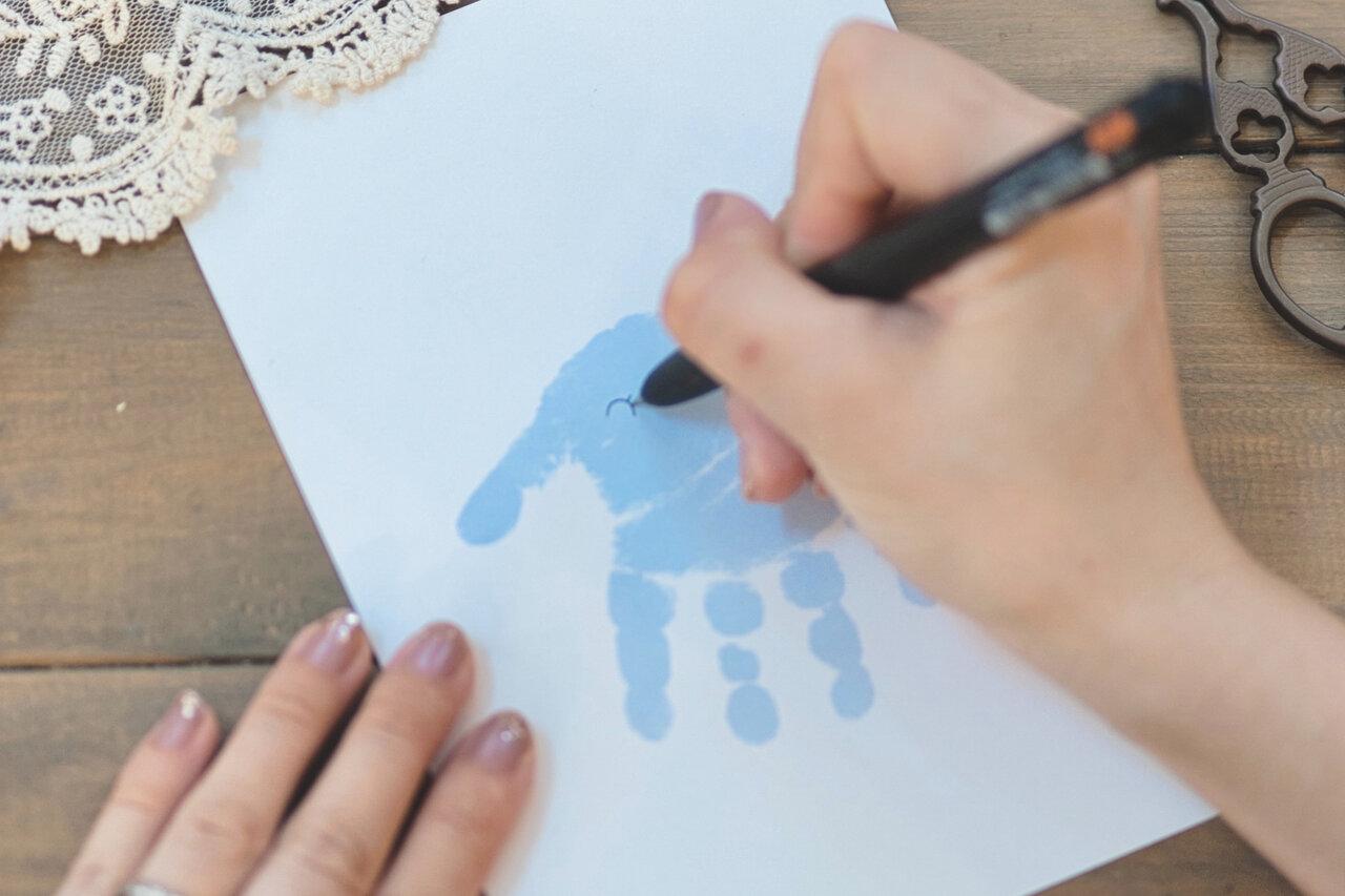 ②手のひらの付け根が上になるように画用紙を置き、黒ペンで親指の付け根にゾウさんの目と耳を描く。  写真:瀬野未知