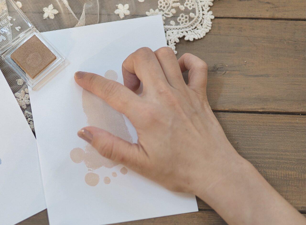 ②足形のかかとが上になるように画用紙を置く。大人の指にインクをつけ、クマの耳と尻尾になるように押す。尻尾は耳よりも少し大きめになるように。  写真:瀬野未知