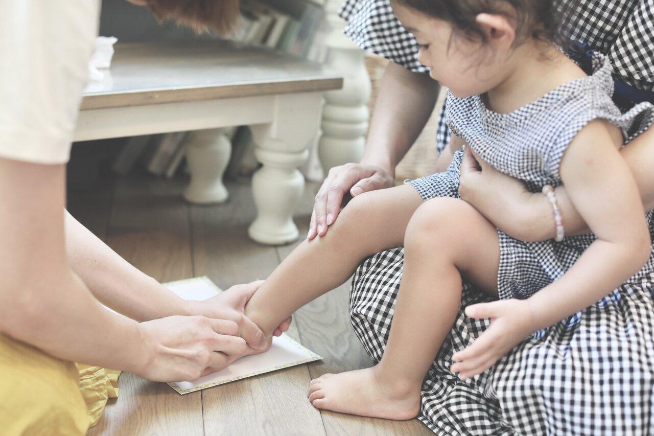 ①子どもの足の裏にインクをたっぷりつけ、画用紙に押し付ける。小さい子どもの場合は、押し付ける力が弱いので、大人が手を添えサポートを。終わったら子どもがインクを舐めないように、すぐにウェットティッシュなどで拭き取る。  写真:瀬野未知