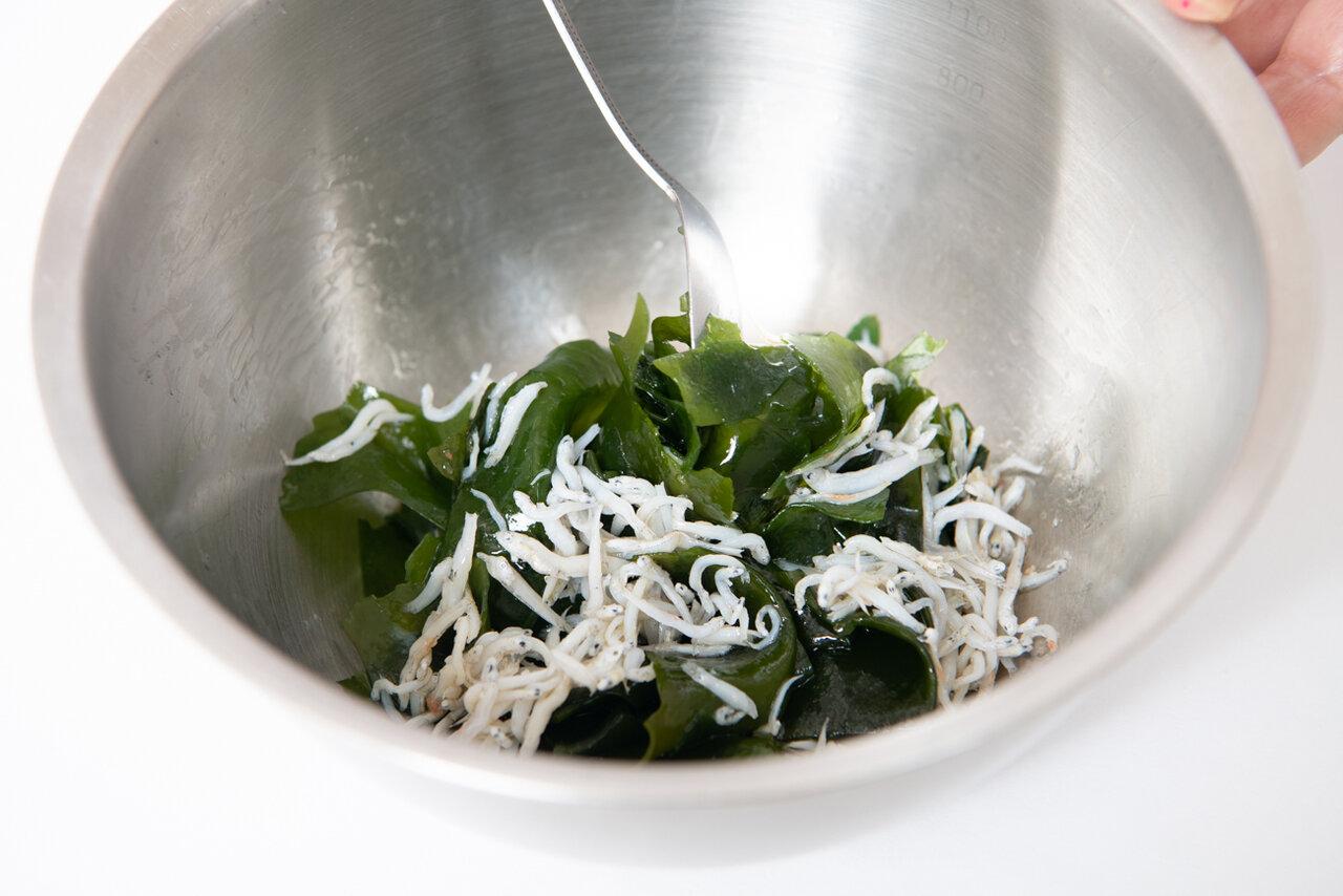 ④ボウルにわかめとしらすを入れて混ぜ、ごま油、塩で味付けしてから、うどんを入れてさらに和える。器に盛り付け、万能ねぎを散らす。  撮影:森﨑一寿美
