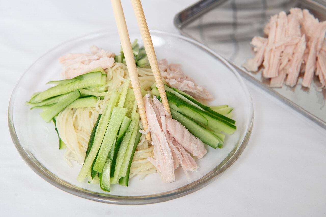 ④器に中華麺を盛り付け、サラダチキンときゅうりをのせる。食べる直前にごまドレッシングをかける。  撮影:森﨑一寿美