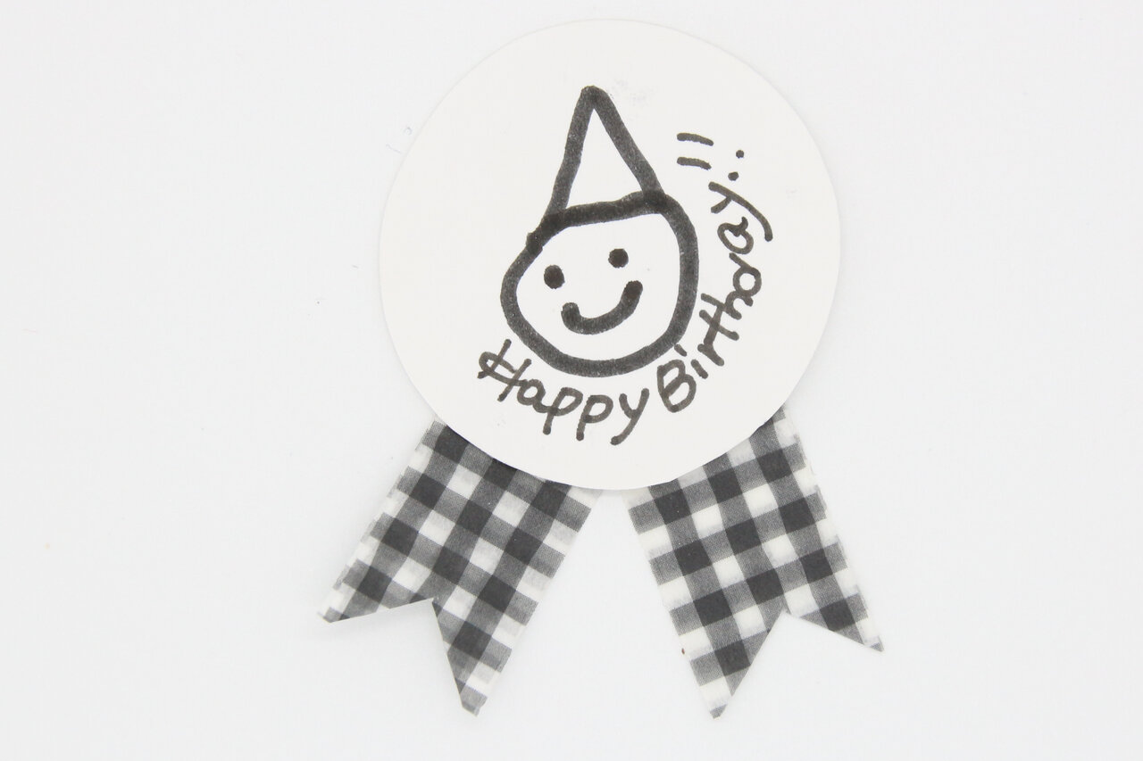 ⑥次は飾り。子どもが描いたイラストに、マスキングテープを貼り付けて、メダル風の飾りを作ります。できたら、小さく切ったクッションテープを裏側に貼り、フォトカードに貼り付けます。  撮影:川上純子