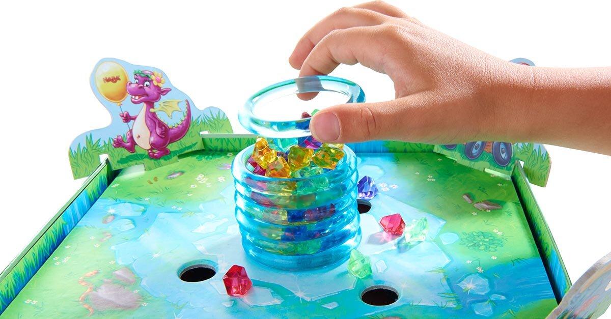 重ねたリングでできた氷の柱の中に、5色の宝石をたっぷりと入れ、上からひとつずつリングを外していくゲーム「きらめく財宝」。  画像提供:すごろくや