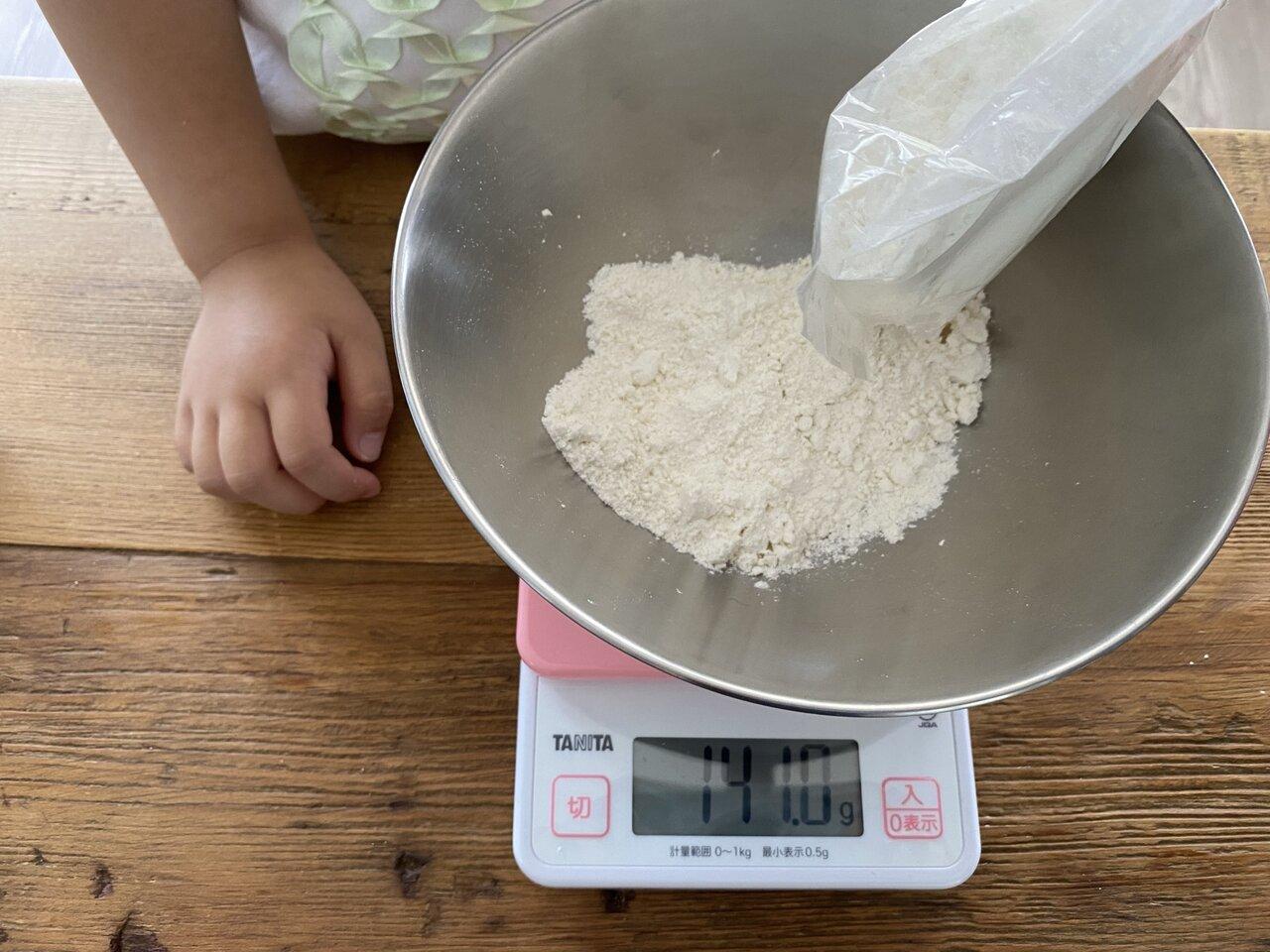 ホットケーキミックスを計量。最近、『ピタゴラスイッチ』(Eテレ)の『100グラムにちょうせん』の影響で、デジタルスケールにハマリ中の娘。