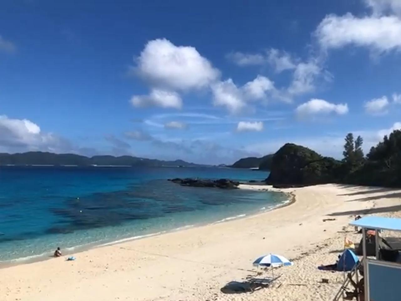 白い砂浜と透明度の高い海が美しい、沖縄・座間味(ざまみ)島の古座間味(ふるざまみ)ビーチ。水面が少し黒っぽくなっている所には、サンゴが生息しています。