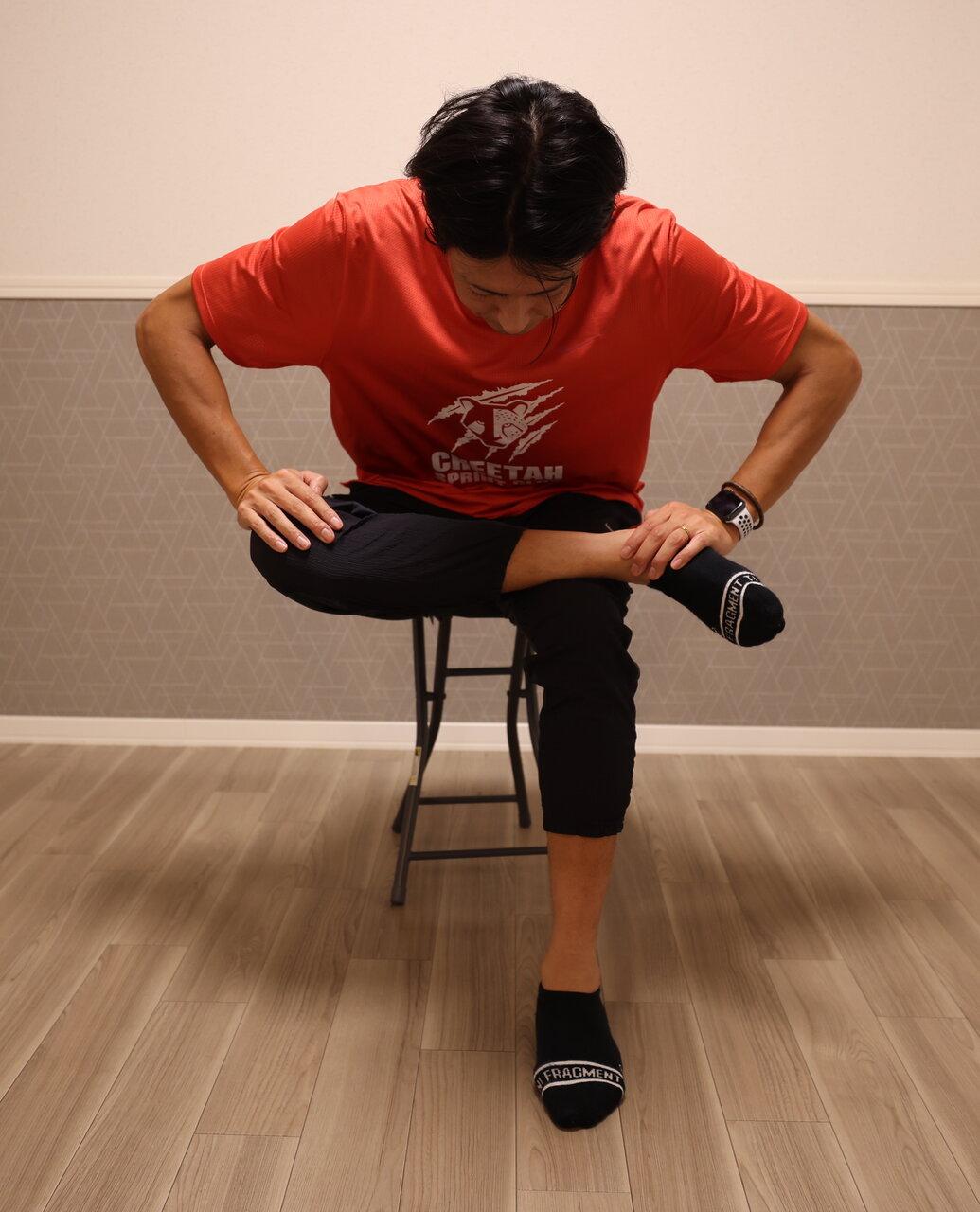 椅子に座ったまま片足ずつあぐらをかくようなイメージでストレッチを。<br> 写真提供:秋本真吾